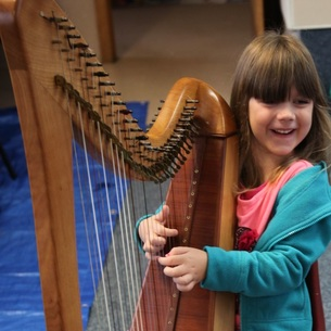 Little girl playing the harp