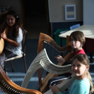 Children learning to play the harp
