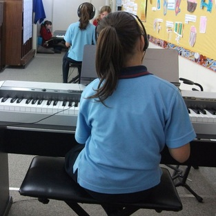 Girl playing keyboard at school